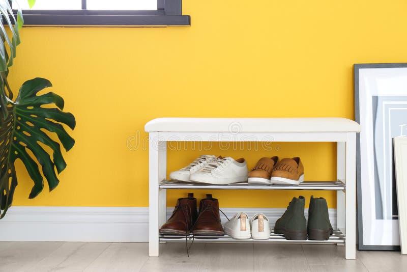 Inzameling van modieuze schoenen bij de rekopslag dichtbij muur in ruimte stock foto