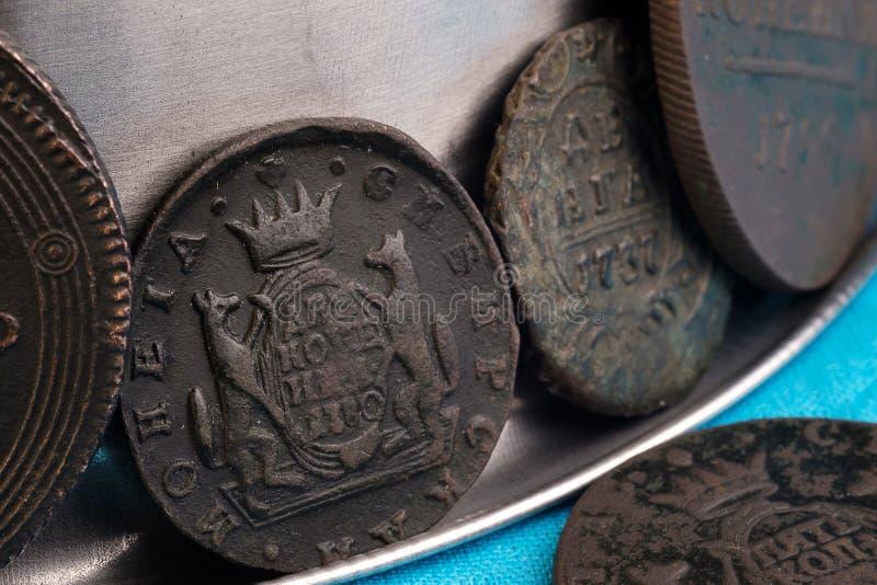 Inzameling van oude Russische muntstukken die in rijen op een metaaloppervlakte worden gestapeld, kopermuntstukken van antiquitei stock foto