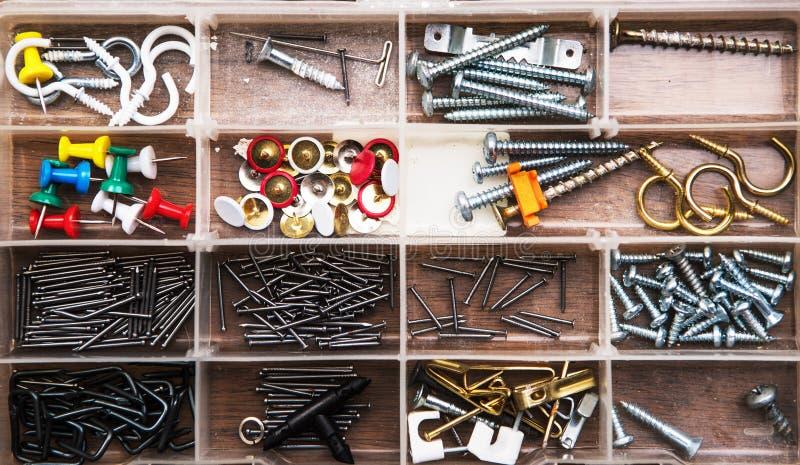 Inzameling van spijkers, duimspijkers, schroeven, haken, spelden, hanger, plastiek en bouten in plastic doos royalty-vrije stock fotografie