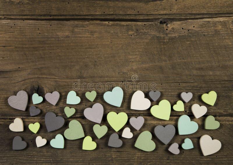 Inzameling van vele met de hand gemaakte harten in natuurlijke kleuren op oud hout royalty-vrije stock afbeeldingen