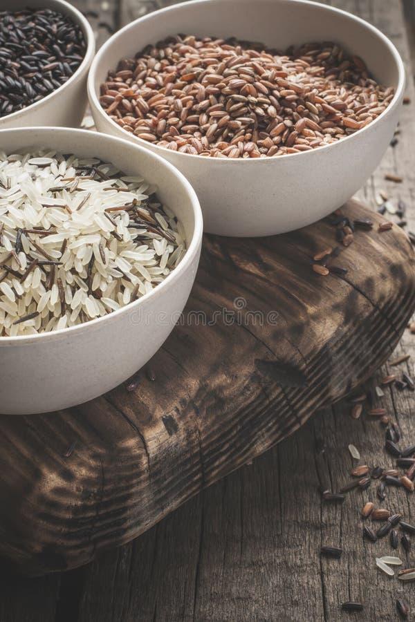 Inzameling van verschillende verscheidenheden van rijst op houten rustieke achtergrond royalty-vrije stock afbeeldingen