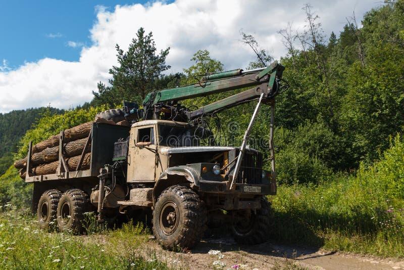 Inzer, Russia - 19 luglio 2014: La macchina di KrAZ per registrare con collega la foresta il giorno di estate soleggiato immagine stock libera da diritti