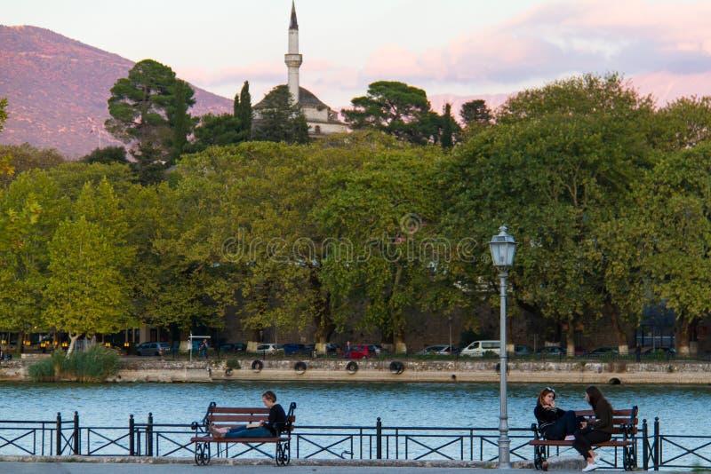 Girls sitting on benches enjoying themselves by lake Pamvotis, I royalty free stock image