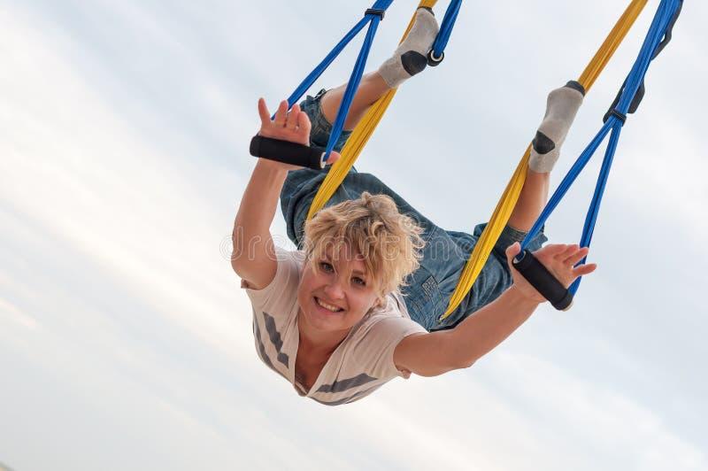 Ioga aérea antigravitante fazendo de cabeça para baixo ou mosca-ioga da jovem mulher na rede no fundo do céu fotos de stock royalty free