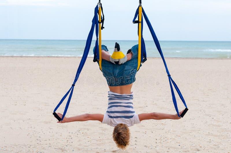 Ioga aérea antigravitante fazendo de cabeça para baixo ou mosca-ioga da jovem mulher na rede no fundo do mar fotografia de stock