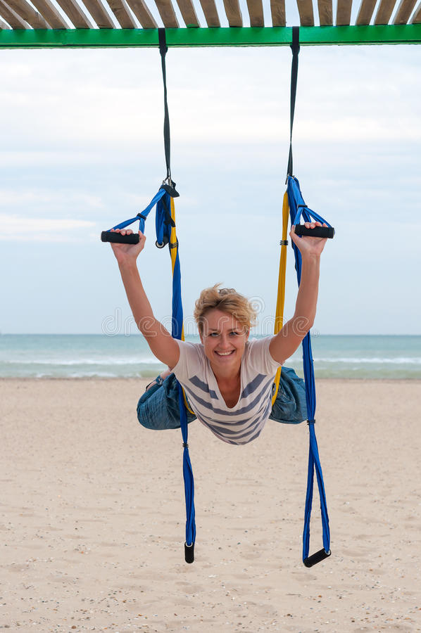 Ioga aérea antigravitante fazendo de cabeça para baixo ou mosca-ioga da jovem mulher na rede no fundo do mar fotografia de stock royalty free