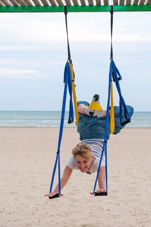 Ioga aérea antigravitante fazendo de cabeça para baixo ou mosca-ioga da jovem mulher na rede no fundo do mar imagens de stock