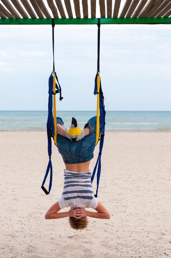 Ioga aérea antigravitante fazendo de cabeça para baixo ou mosca-ioga da jovem mulher na rede no fundo do mar fotos de stock