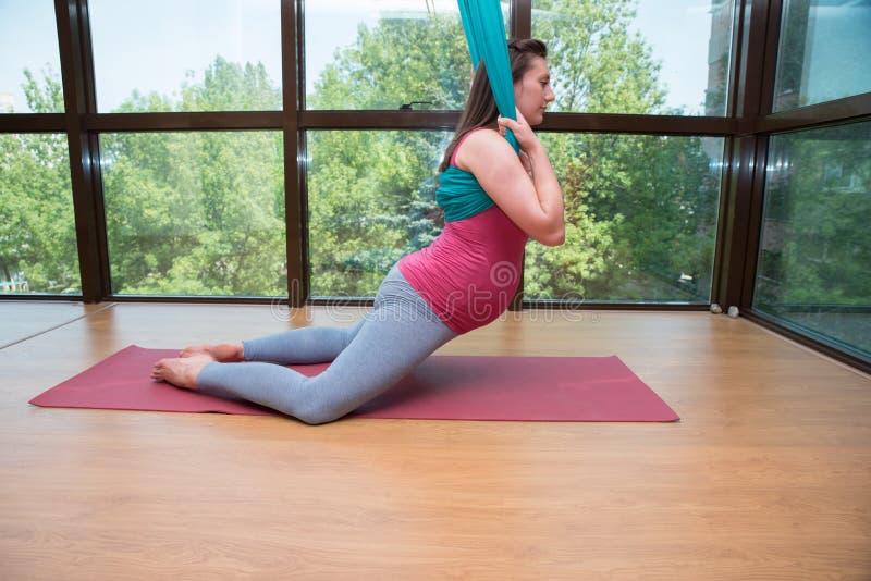 A ioga aérea da mulher gravida nova exercita a ioga interna da mosca imagem de stock royalty free