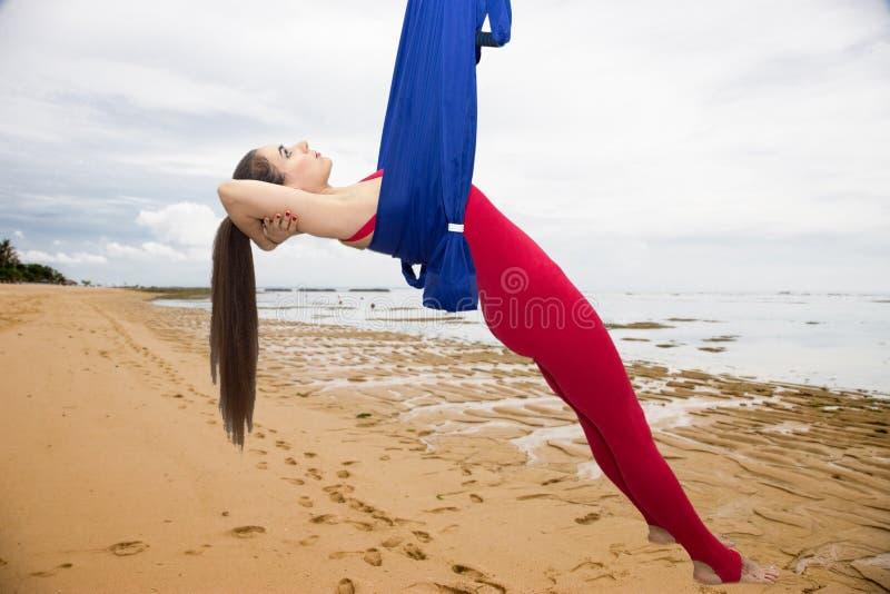 Ioga aérea ou ioga antigravitante Asana praticando da ioga da mosca da jovem mulher fora imagem de stock royalty free