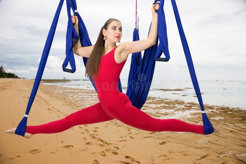 Ioga aérea ou ioga antigravitante Asana praticando da ioga da mosca da jovem mulher fora foto de stock