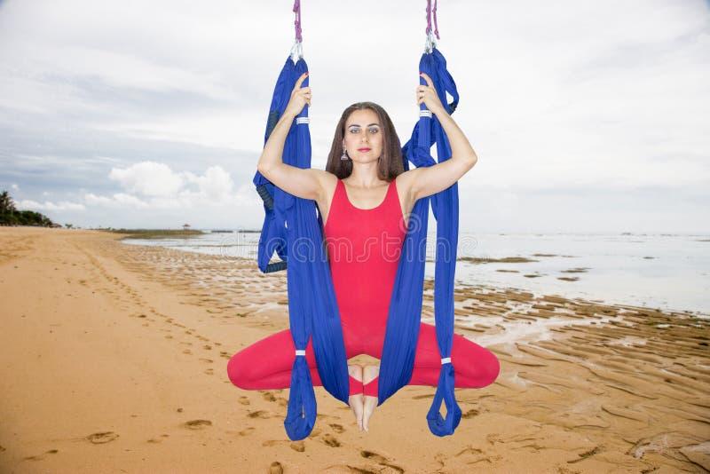 Ioga aérea ou ioga antigravitante Asana praticando da ioga da mosca da jovem mulher fora foto de stock royalty free