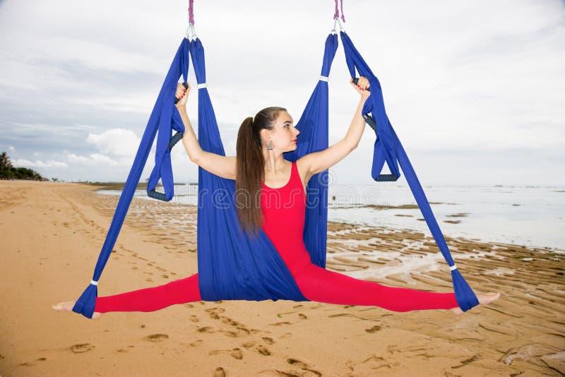 Ioga aérea ou ioga antigravitante Asana praticando da ioga da mosca da jovem mulher fora fotografia de stock
