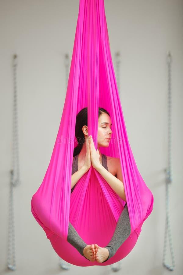 Ioga antigravitante aérea da pose dos lótus da menina A mulher senta-se na rede fotografia de stock royalty free
