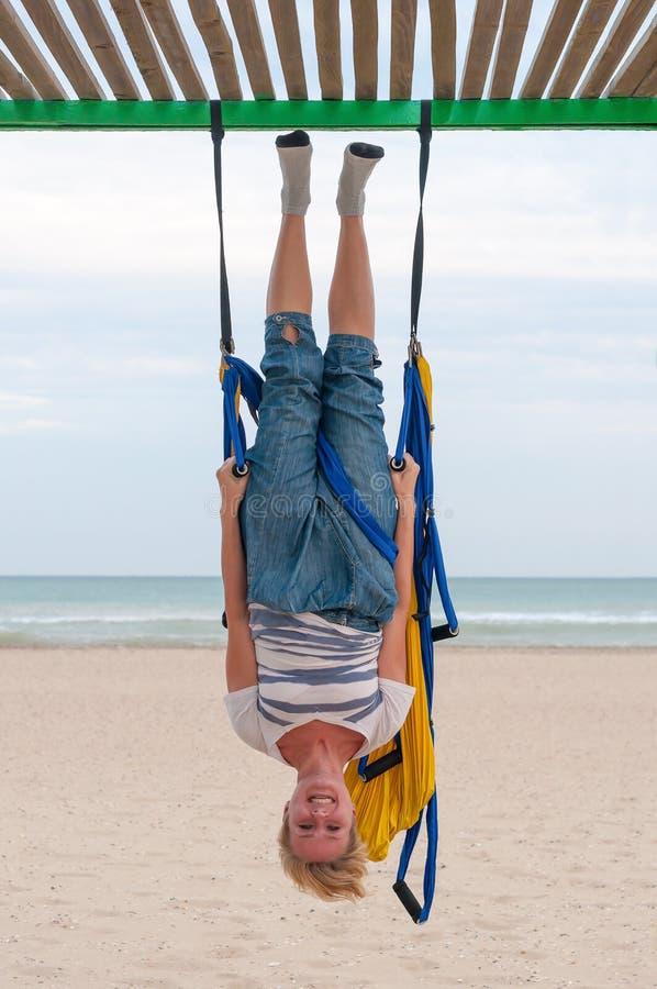 A ioga antigravitante, menina que faz a ioga exercita na praia Ioga da mosca imagens de stock royalty free