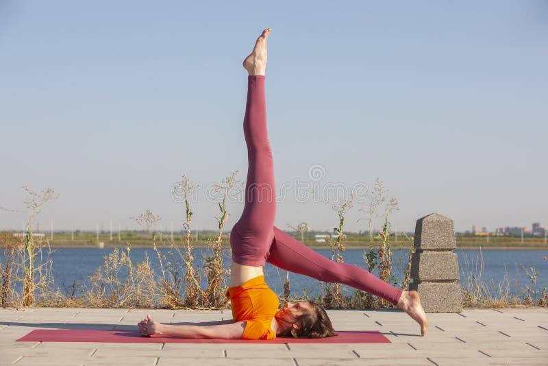 Ioga ao ar livre A mulher feliz que faz exerc?cios da ioga, medita no parque Medita??o da ioga na natureza Conceito do estilo de  fotografia de stock royalty free
