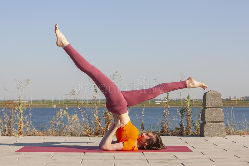 Ioga ao ar livre A mulher feliz que faz exerc?cios da ioga, medita no parque Medita??o da ioga na natureza Conceito do estilo de  fotos de stock