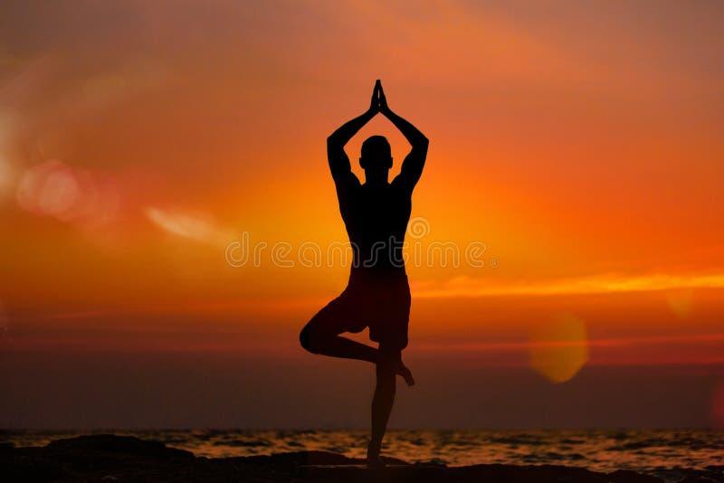 Ioga apta do vrikshasana das práticas do homem novo na praia do verão no por do sol imagens de stock