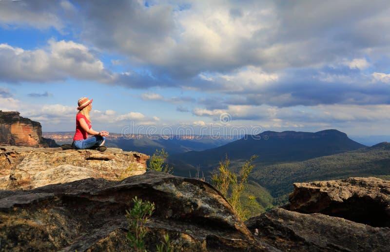 Ioga calma da mulher na cimeira da montanha imagens de stock