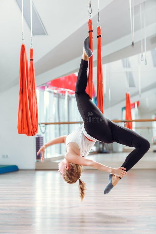 Ioga da mosca A jovem mulher pratica a ioga antigravitante aérea com uma rede imagens de stock royalty free