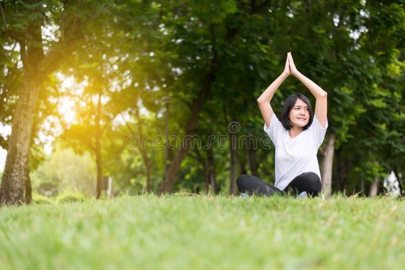 Ioga da mulher asiática no parque na manhã, feliz praticando e no sorriso, em pensamento do positivo conceito, em saudável e no e foto de stock