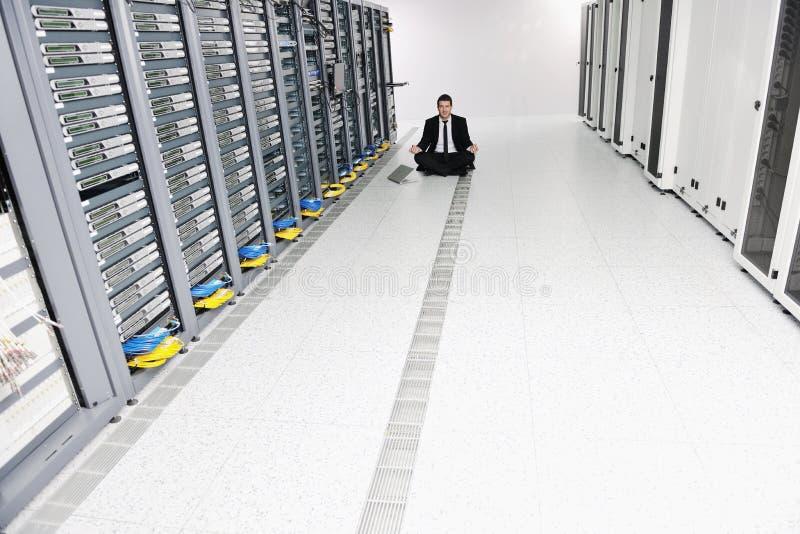 Ioga da prática do homem de negócio no quarto do server de rede foto de stock