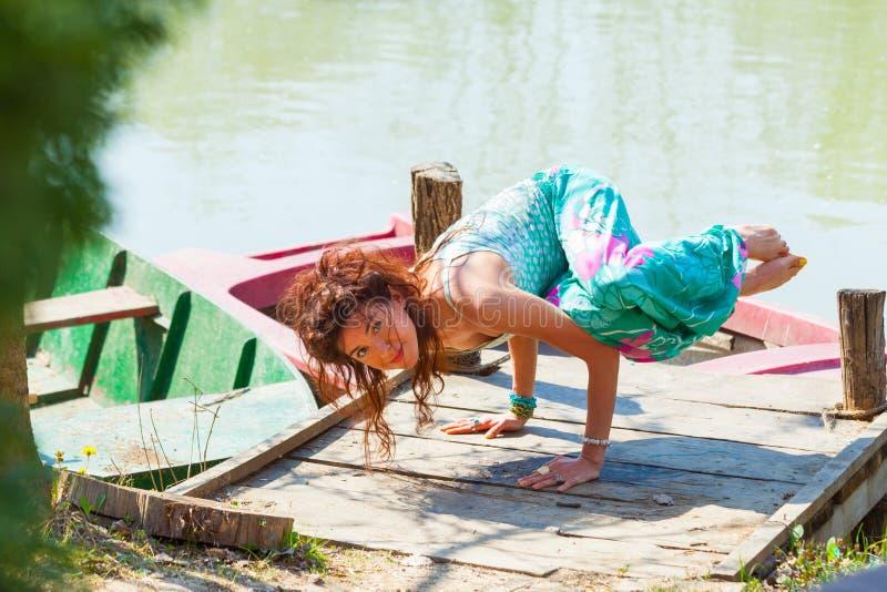 Ioga da prática da jovem mulher exterior pela pose do equilíbrio do lago no conceito saudável do estilo de vida das mãos fotos de stock royalty free