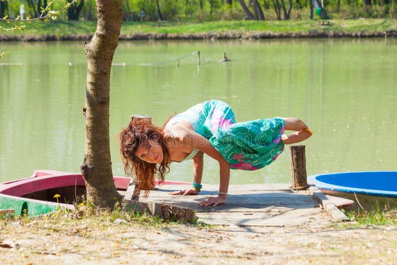 Ioga da pr?tica da jovem mulher exterior pela pose do equil?brio do lago no conceito saud?vel do estilo de vida das m?os foto de stock royalty free