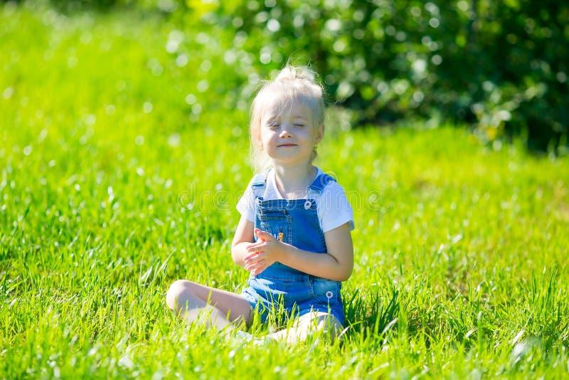 Ioga das práticas da menina na grama verde fotografia de stock