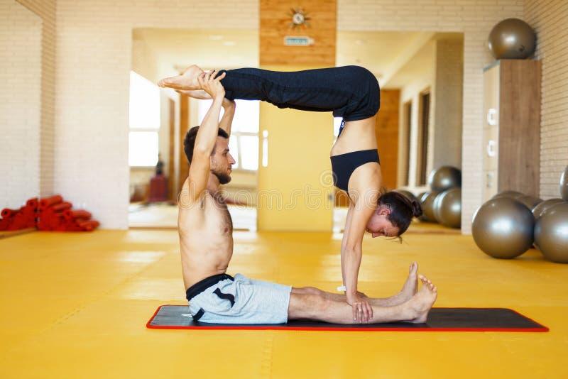 A ioga de Acro, dois povos desportivos pratica a ioga nos pares, fazer dos pares fotos de stock