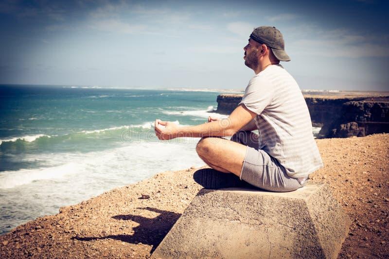 Ioga do exercício do homem na costa da praia imagem de stock royalty free
