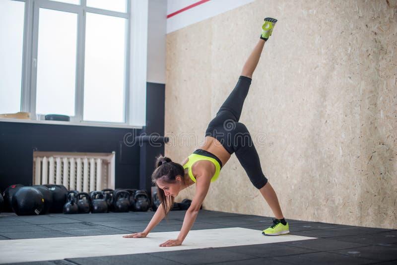 A ioga do performin da jovem mulher no gym, coube a fêmea que faz esticando exercícios na esteira fotos de stock royalty free