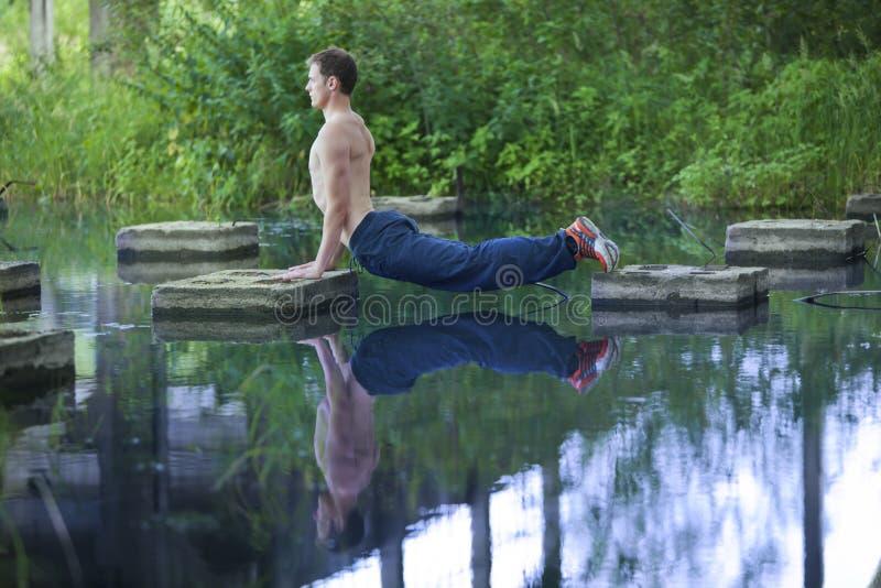 Ioga - equipe e sua reflexão na água imagens de stock royalty free