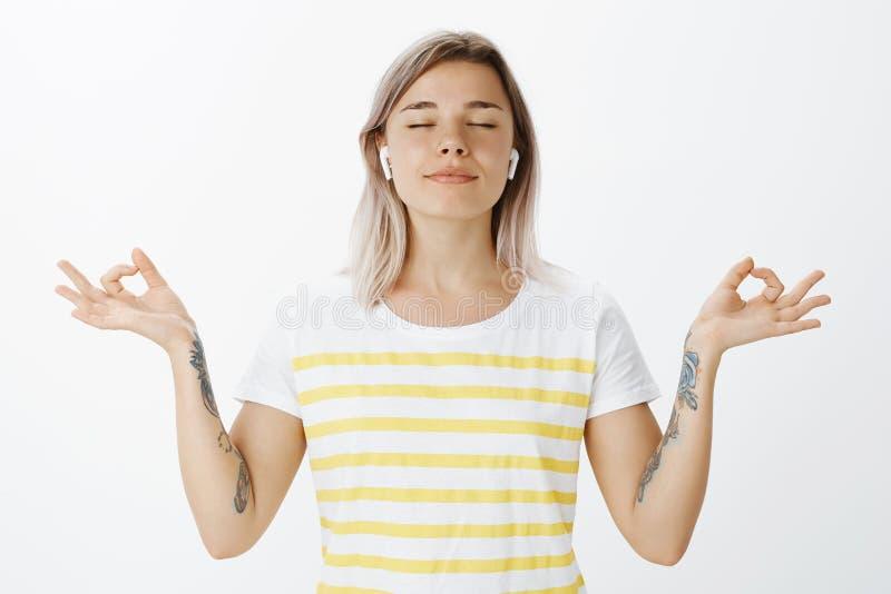 Ioga, estilo de vida e conceito da juventude Retrato da mulher atrativa alegre relaxado em fones de ouvido sem fio, estando com fotos de stock
