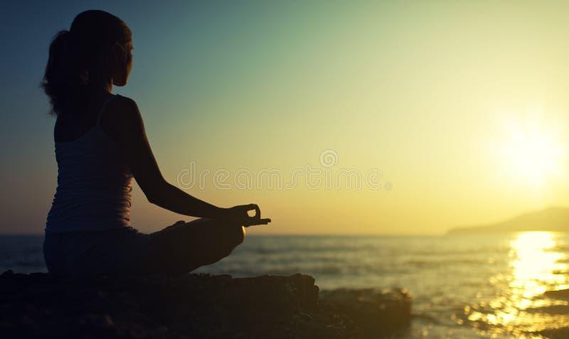 Ioga fora. silhueta de uma mulher que senta-se em uma posição de lótus imagens de stock