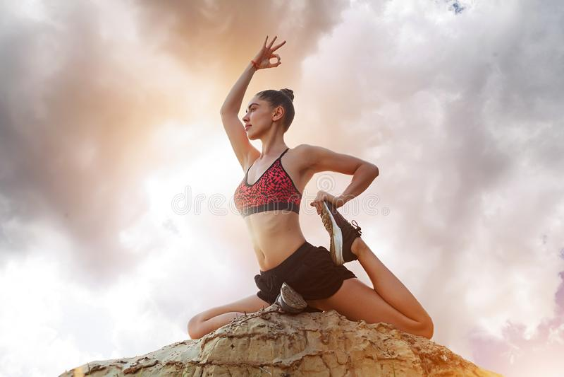 Ioga, harmonia da saúde, ioga praticando da mulher em um fundo de nuvens dramáticas bonitas com um sol brilhante imagem de stock