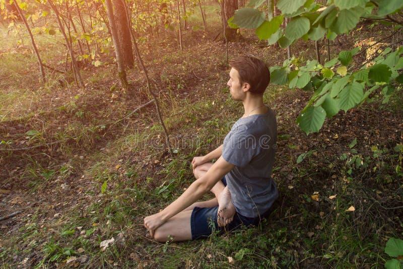 Ioga, homem na meditação da pose dos lótus, fora na natureza, espaço da cópia imagem de stock