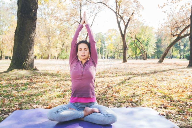 Ioga meditando e praticando da jovem mulher saudável exterior imagens de stock royalty free