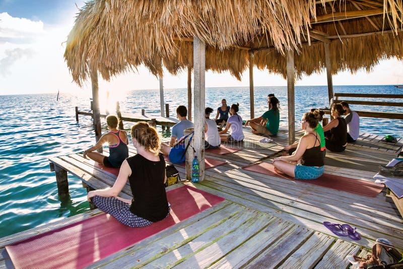 Ioga na doca da ilha do calafate de Caye, Belize fotografia de stock