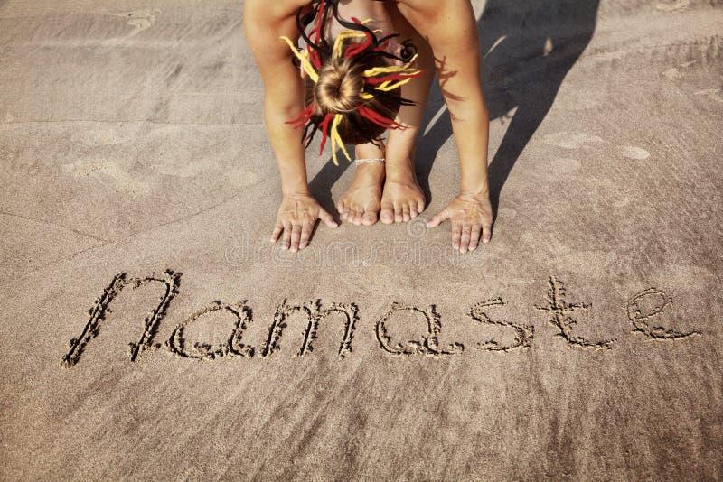 Ioga na praia com Namaste fotos de stock