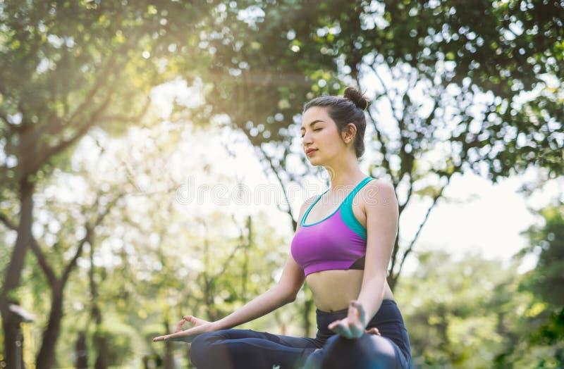 Ioga no exercício saudável do parque a mulher faz a pose da ioga dos lótus fotos de stock royalty free