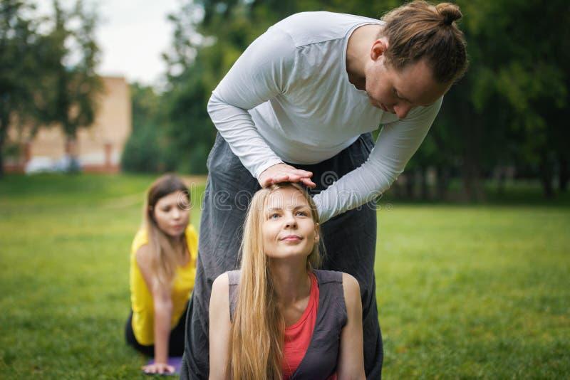 Ioga no parque da manhã - o instrutor está treinando jovens mulheres para a flexibilidade imagens de stock