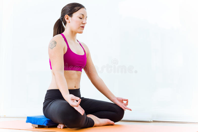 A ioga praticando da jovem mulher bonita em casa nos lótus postula fotos de stock
