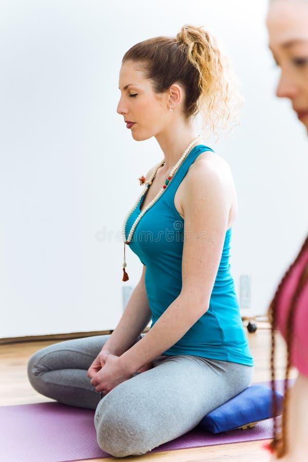 Ioga praticando da jovem mulher bonita em casa Pose de Vajrasana imagem de stock royalty free