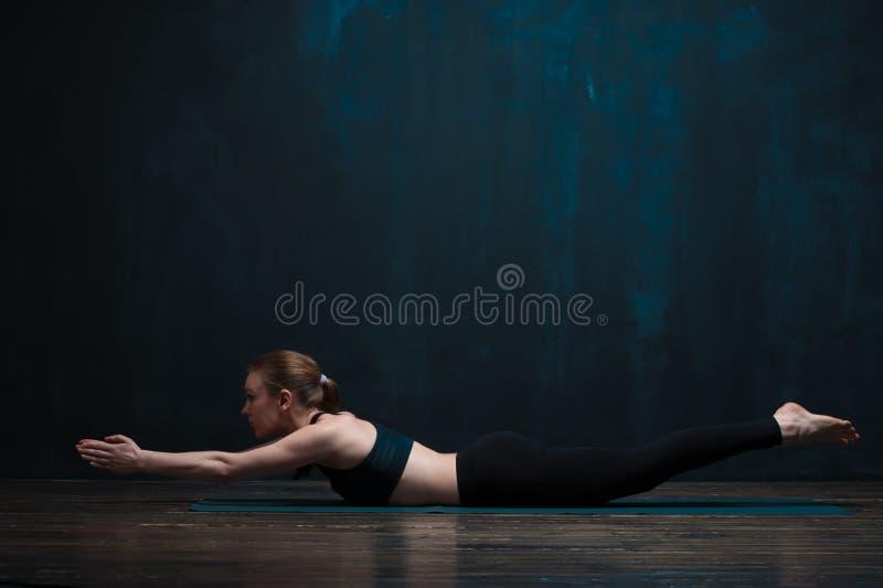 Ioga praticando da jovem mulher contra a parede escura fotografia de stock royalty free