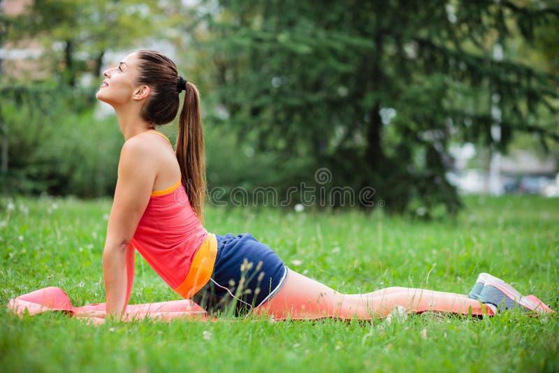 Ioga praticando da jovem mulher do ajuste no parque da cidade fotos de stock