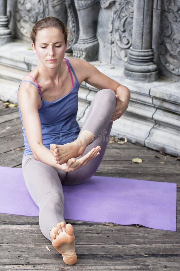 Ioga praticando da jovem mulher durante a retirada da ioga em Ásia, Bali, meditação, abrandamento no templo abandonado imagem de stock