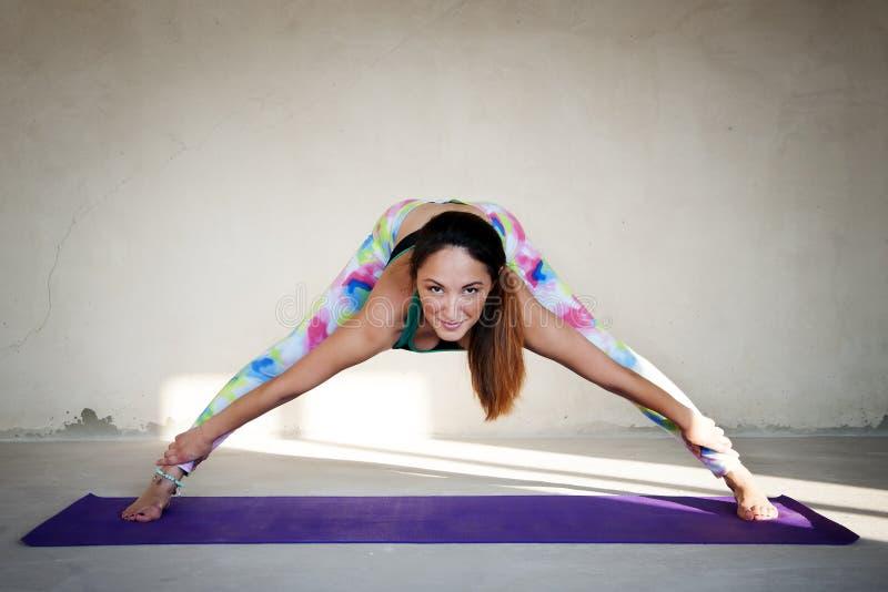 Ioga praticando da jovem mulher em um fundo urbano foto de stock royalty free