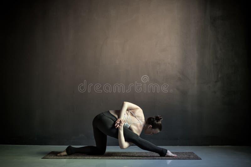 Ioga praticando da jovem mulher, estando no exerc?cio de Utthita Trikonasana imagem de stock royalty free