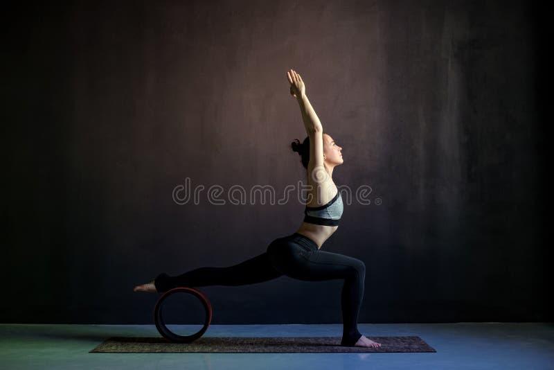 Ioga praticando da jovem mulher, estando no exerc?cio do guerreiro um, Virabhadrasana imagens de stock